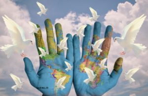 A world community painted on hands with doves